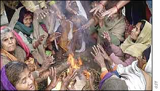 Municipal workers warm themselves around a fire in Delhi