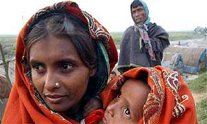 Mother holds her warmly wrapped baby outside Dhaka