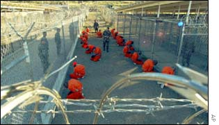 Detainees in orange jumpsuits sit in a holding area at Camp X-Ray