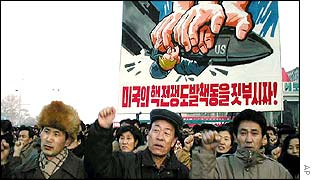 North Koreans in front of anti-US poster