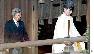 Japanese Prime Minister Junichiro Koizumi (left) follows a Shinto priest as the prime minister visits Yasukuni shrine, 14 Jan 2003