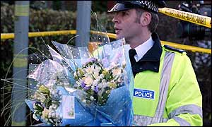 A policeman brings flowers to the scene where Detective Constable Stephen Oake died