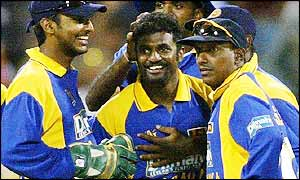 Muttiah Muralitharan (centre) is congratulated by his jubilant team-mates Kumar Sangakkara (left) and Aravinda De Silva