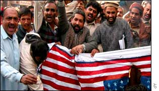 Protesters burn a US flag during a rally in Multan in protest at INS policy