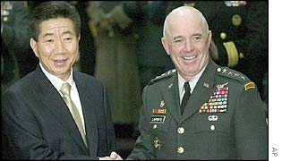 Roh Moo-hyun, left, shakes hands with US Gen Leon LaPorte, Korea-US Combined Forces Command