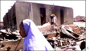 A Nigerian woman passes a razed church in Kaduna
