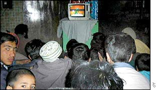 Kabul residents watch a TV in a video shop
