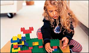 A girl playing with Lego bricks