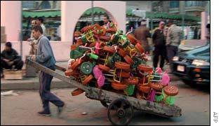An Iraqi street vendor pulling a cart full of plastic toys at a Baghdad market