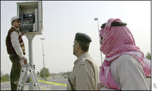 Kuwaiti police remove the film from a traffic camera near the intersection where two Americans were ambushed