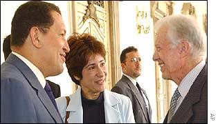 Hugo Chavez, left, accompanied by a translator, meets Jimmy Carter, right