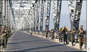 Indian troops patrol a bridge in Gauhati, Assam