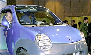 President of Japans car and motorcycle maker Suzuki Masao Toda (at the wheels) and his successor Hiroshi Tsuda (L) introduce its new small car Twin in Tokyo, 22 January 2003