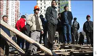More than 100 construction workers barricade the entrance to the Greenland Gardens housing complex in Beijing  on Friday 17 January