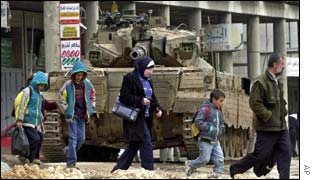 Palestinians walk in front of an Israeli tank in the West Bank town of Nablus