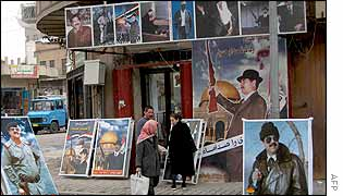 Iraqis pass by a shop displaying pictures of Iraqi President Saddam Hussein in Baghdad 20 January 2003.