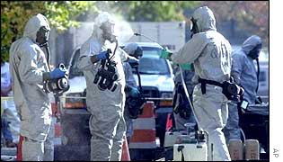 Hazardous material workers decontaminate each other