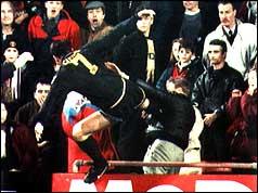 Cantona lanches his karate kick at Simmons