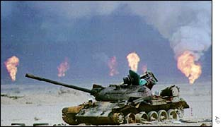 Burnt out tank in front of burning oil wells at end of 1991 Gulf War