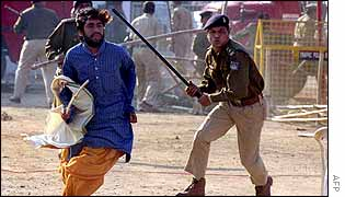 A policeman runs after a Hindu priest in Bhopal, 23 January 2003