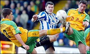 Dagenham's Steve West (centre) is challenged by Norwich's Adam Drury (left) and Malky Mackay