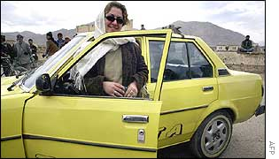 Hirama poses by a car after a driving test in Kabul