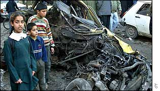 Children look at the wreckage of a car