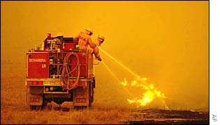 Firefighters put out a spot fire as they battle bush fires heading for the town of Omeo in the Alpine region in Victoria state