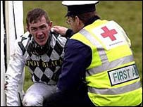 Tony McCoy is treated by a first aid officer after taking a tumble
