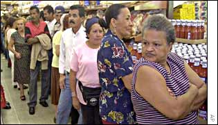 Maria Mijares, right, waits in line with other customers for bread to arrive at the supermarket in Caracas, Venezuela