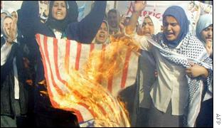 Iraqi school girls burn a US flag during an anti-US protest in Baghdad