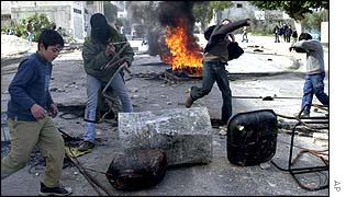 Palestinian schoolchildren throwing stones at a roadblock
