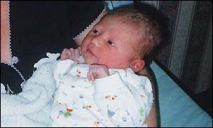Mum cradles newborn baby