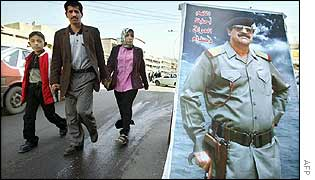 Iraqi family walk past poster of Saddam Hussein