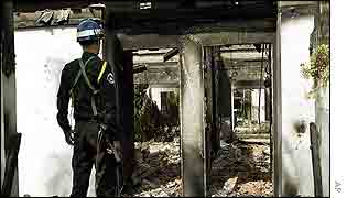 Cambodian policeman surveys a burnt-out Thai hotel