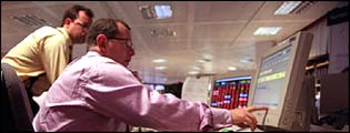 Stockbrokers on dealing desk in the city, FTSE 100 index in background