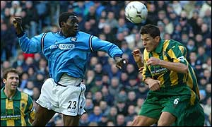 West Brom's Phil Gilchrist (right) puts through his own net under pressure from Marc-Vivien Foe