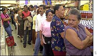 Venezuelans queue in a supermarket