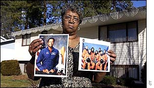 Family friend of Michael Anderson holds pictures of the astronauts outside her home