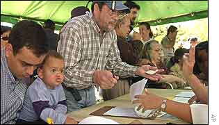 Cristobal Abreu, left, signs a petition as his son Jesus, 2, looks on in Caracas, Venezuela
