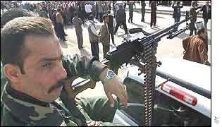 An Iraqi soldier manning a mounted machine gun watches protesters passing by during an anti-US demonstration in Baghdad