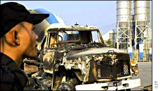 A guard stands next to a burnt truck at the Thai-owned Siam Cement Cambodia company