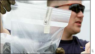 Environmental Protection Agency contract worker Trey Smith labels bagged space shuttle debris cleared from a school in Texas 3 Feb 2003