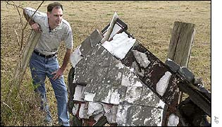A local resident examines a piece of debris that fell near his home