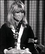 Julie Christie with her Oscar and a BBC reporter's hand and microphone in 1966