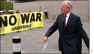 Australian Prime Minister John Howard walks past an anti-war sign at the Australian Parliament in Canberra