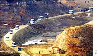 A convoy of North Korean buses crosses into South Korean territory to take the South Koreans back to the North