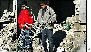 Boys inspect the rubble of the house of Baha Saeed whose mother was crushed inside.