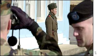 US soldiers watch North Korean soldier through binoculars in demilitarised zone
