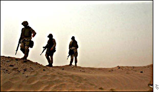US marines stand on a dune during a sand storm in the Kuwaiti desert